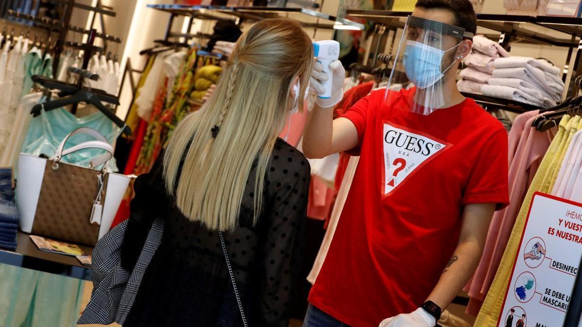 Un treballador d'una botiga de roba controla la temperatura a una clienta