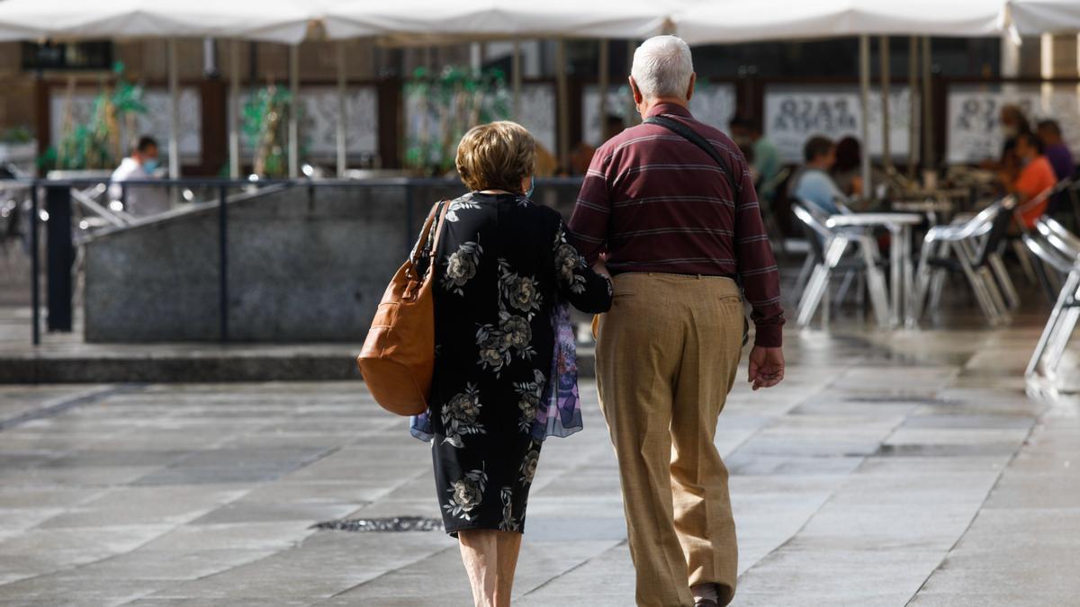 Una pareja de personas mayores pasea por una plaza