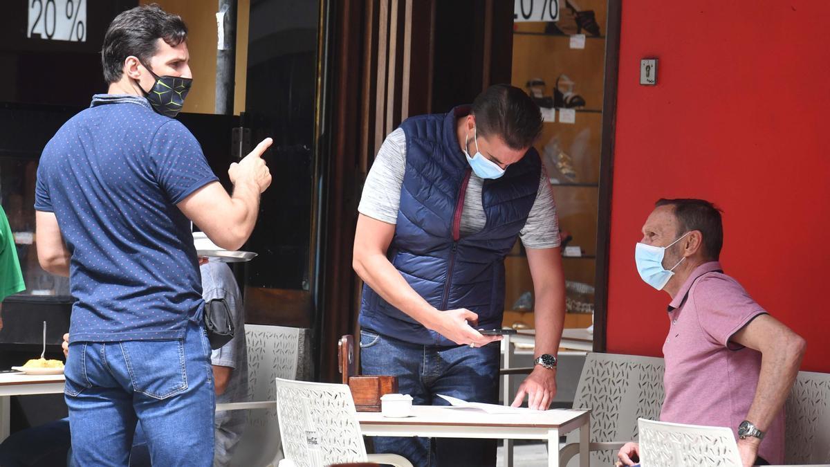 Tres hombres con mascarilla en una terraza coruñesa.