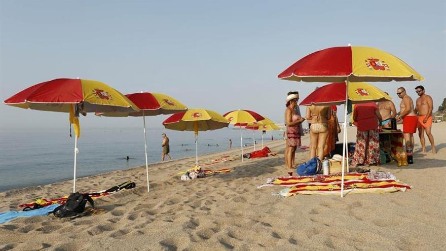 Plantan doce sombrillas con los colores de España en una playa de Barcelona
