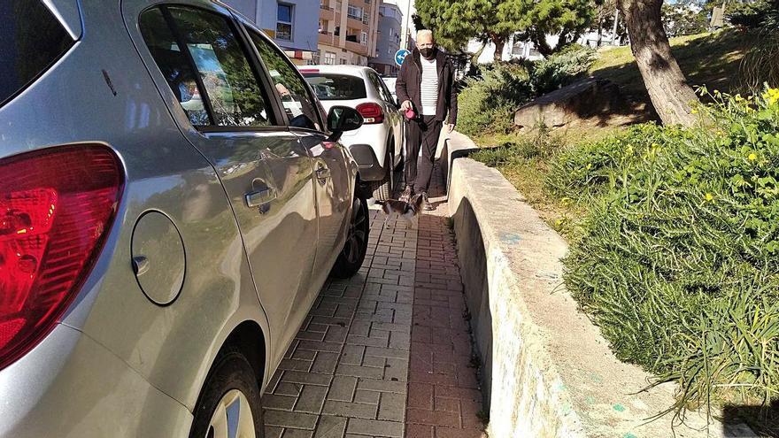 Salvador Tineo, vecino del Ejido, ayer, pasea con su perro por las estrechas aceras de la calle Diego de Siloé, todo el año con coches subidos a las aceras.