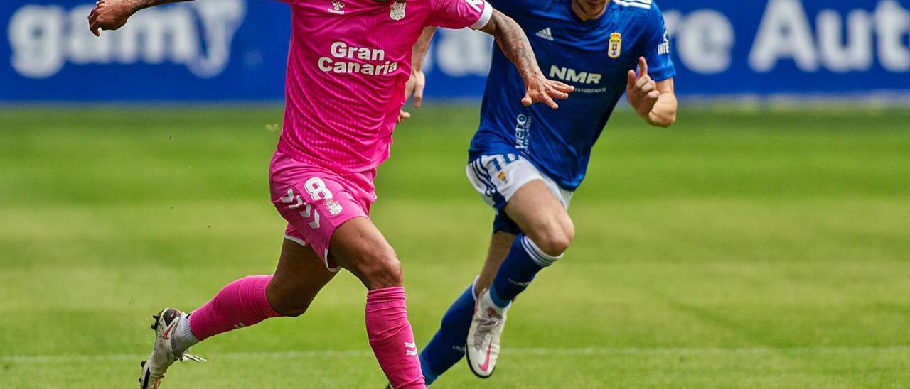 El tinerfeño Maikel Mesa arranca con el esférico, pegado en a bota derecha, ante la presión del centrocampista del Oviedo Borja  Sánchez.  | | LOF