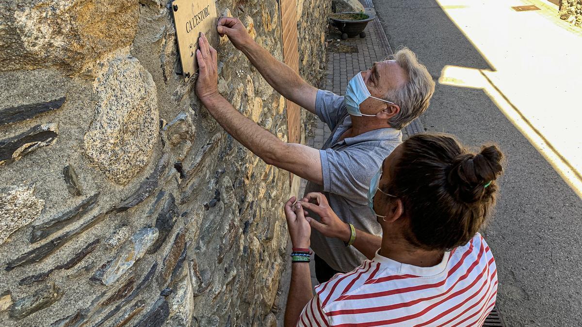 Operaris de l'Ajuntament instal·len un dels rètols de les cases antigues de la vila