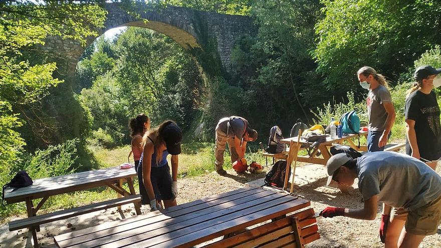 Els joves van començar ahir els treballs pintant els bancs de la zona d'oci del pont   ANDREA IZQUIERDO