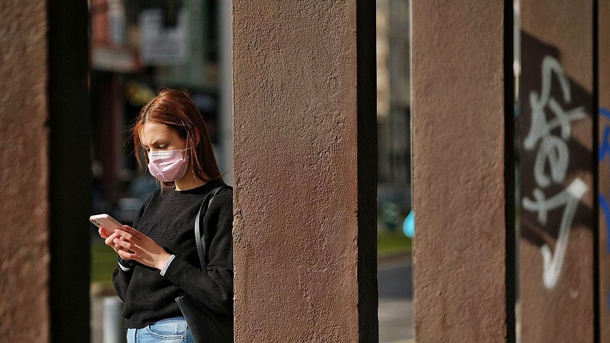 Una mujer lee mensajes en su móvil.
