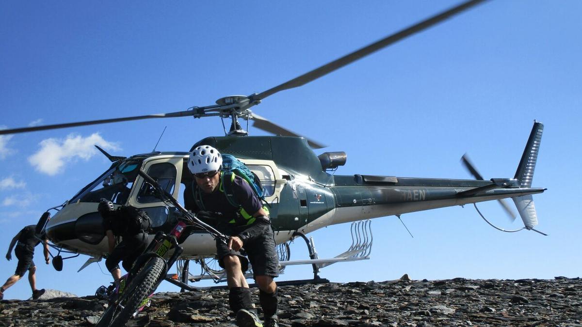 Un aficionado a la bici de montaña baja del helicóptero en Punta Suelza.