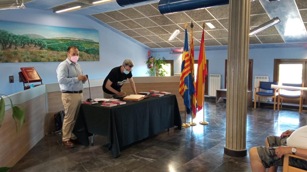 Jesús Maestro firma en el libro de visitas del Ayuntamiento de Magallón en presencia de su alcalde, Víctor Chueca.