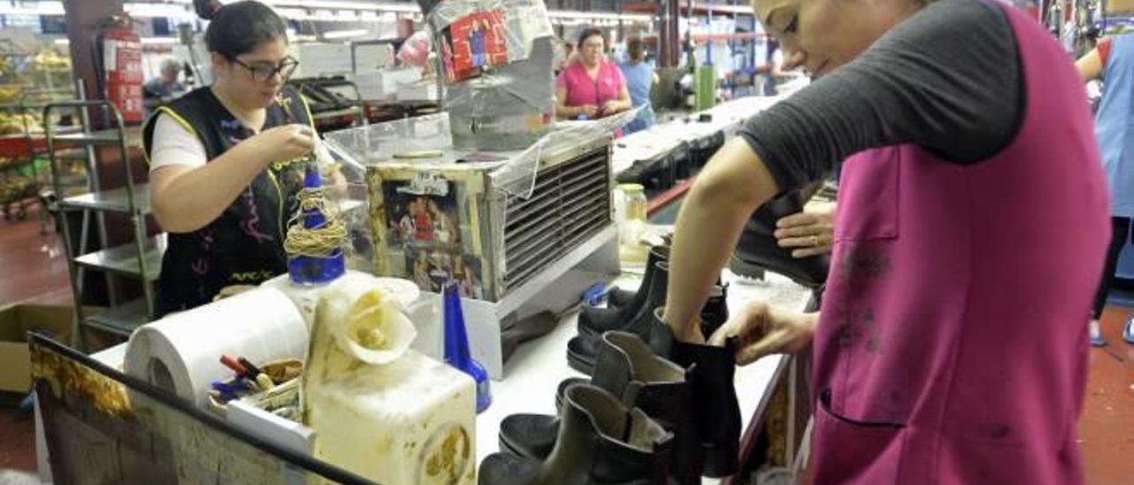 Trabajadoras de una empresa de calzado de la provincia repasando botines de invierno.