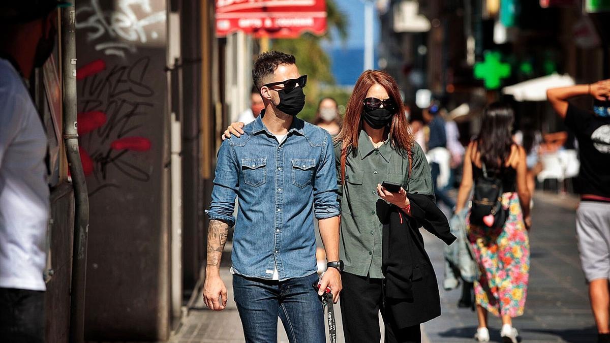 Una pareja pasea por la céntrica calle Castillo con mascarilla en el primer día de flexibilización de las medidas en exteriores