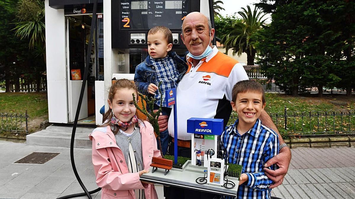 El gasolinero Francisco Raposo posa junto a sus nietos, ayer en su último día de trabajo.   | // VÍCTOR ECHAVE