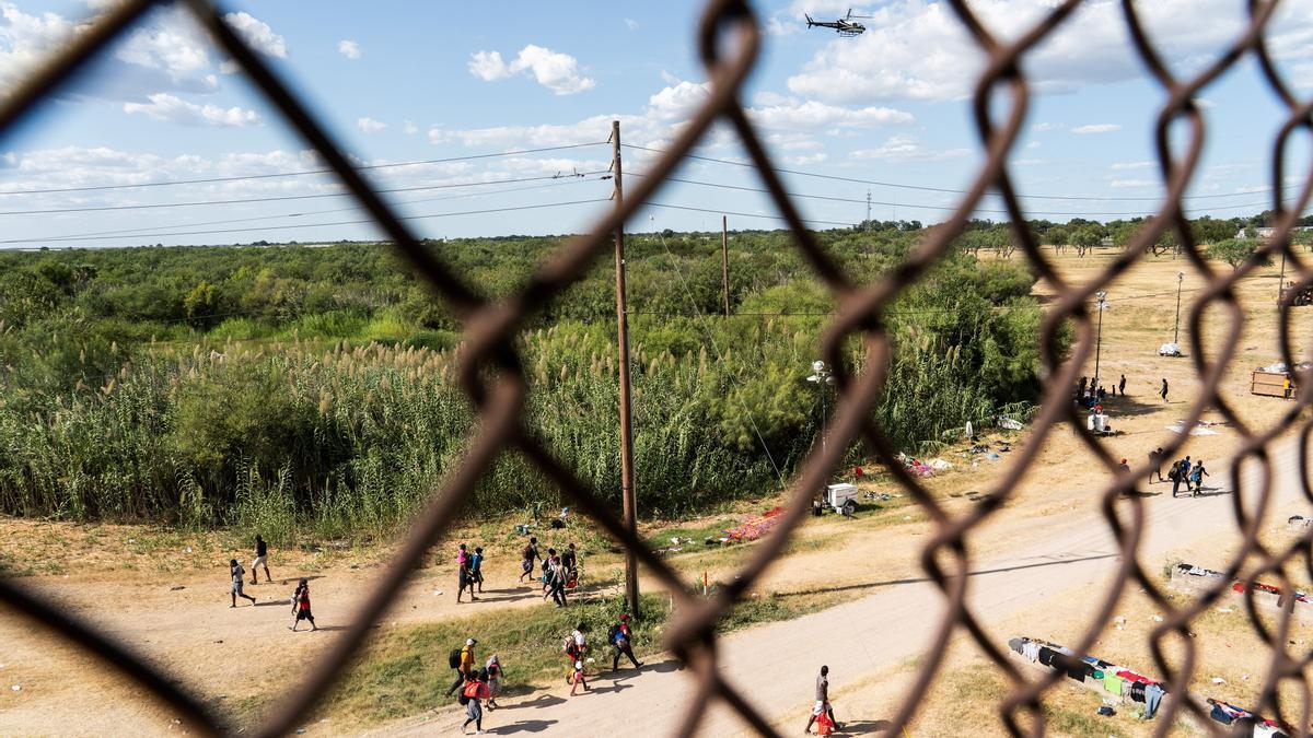 Grupos de migrantes esperan para pasar a Estados Unidos desde México.