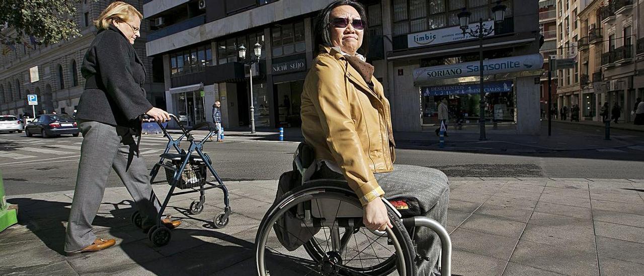 Paloma (en silla de ruedas) y Ana en una imagen de 2016 al  lado del  edifico donde ocurrió la tragedia.  |