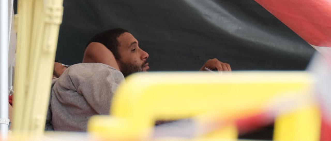 Un joven llegado en patera descansa en una de la carpas instaladas en el muelle de Arguineguín.