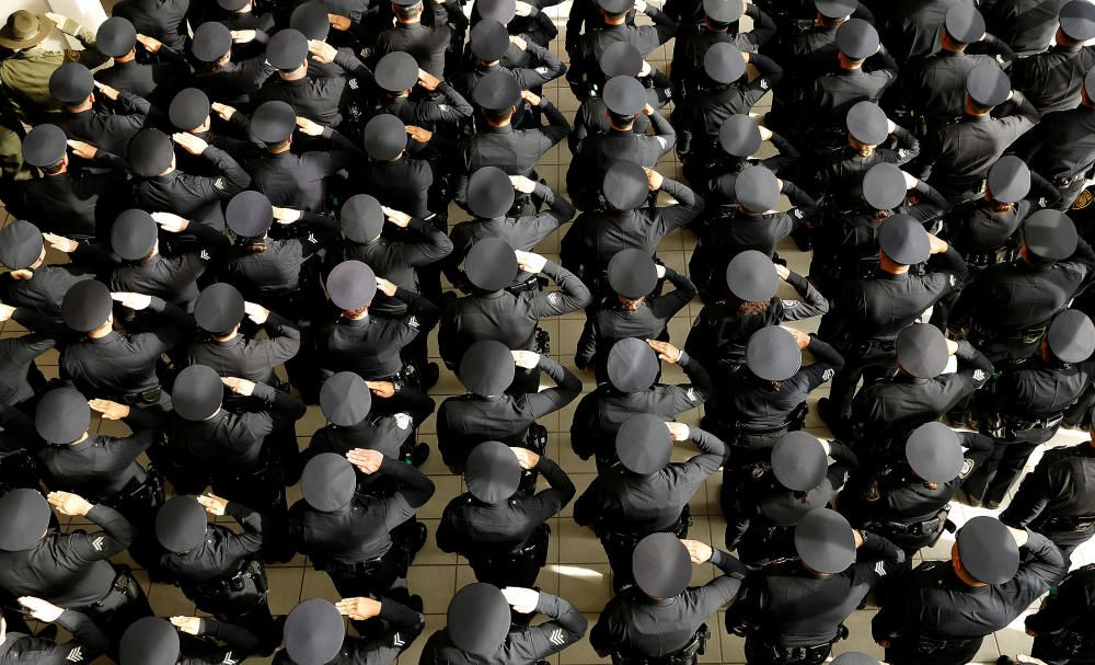 Officers stand at attention as a casket passes ...