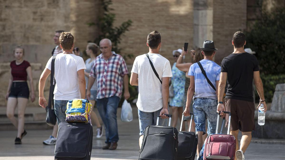 Varias personas arrastran sus maletas por la calle.