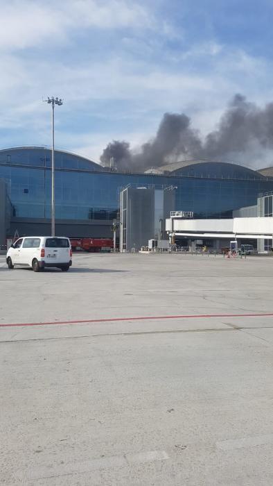 Los bomberos de la propia terminal trabajan en la cubierta y el humo es muy denso pero siguen saliendo vuelos