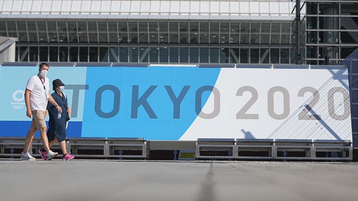 Ciudadanos en Japón caminan junto a un cartel de los Juegos Olímpicos de Tokio 2020