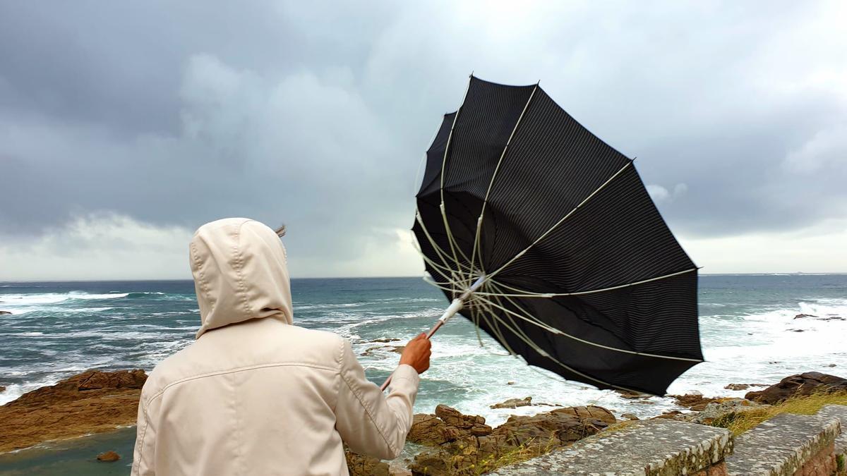 Una mujer sostiene un paraguas llevado por el viento en el paseo de Monterreal, en Baiona.