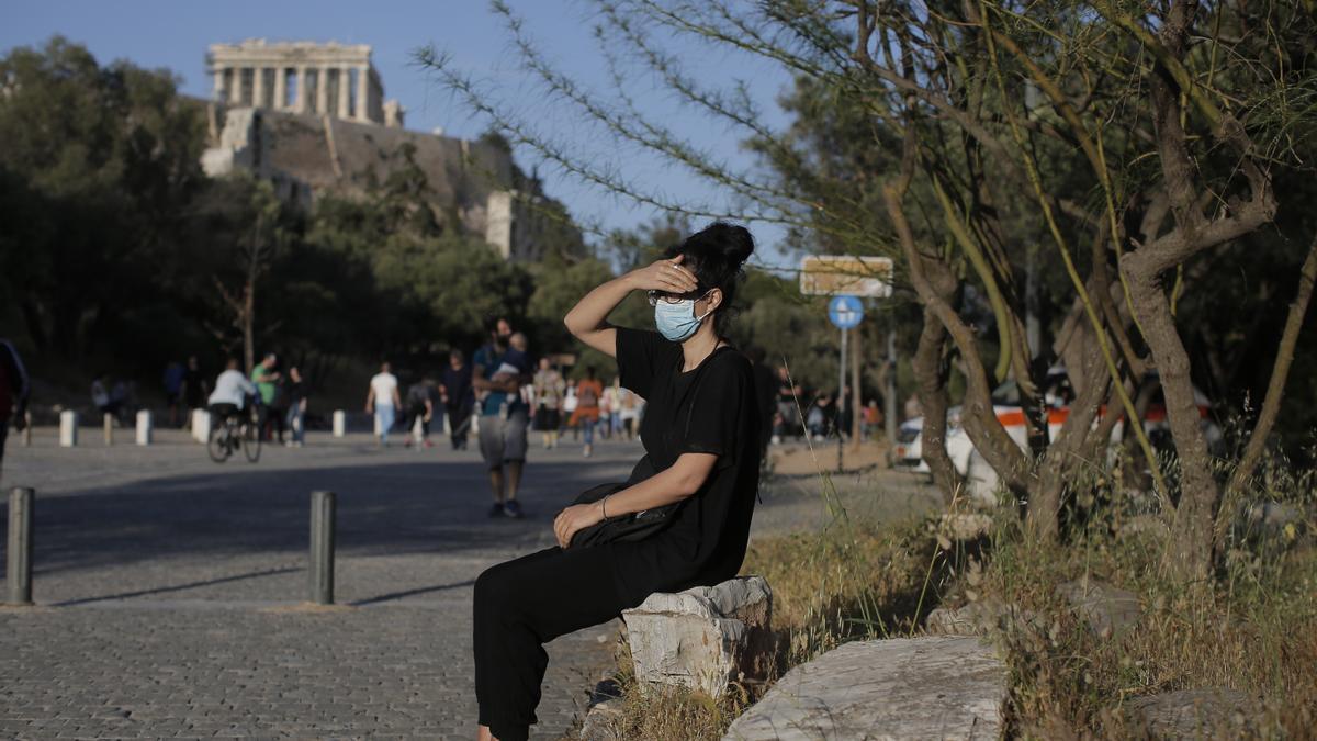 Una joven con mascarilla en el centro de Atenas