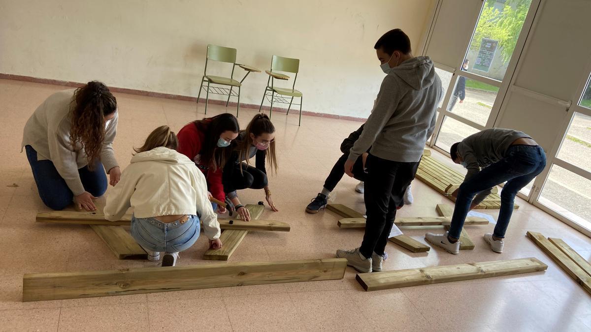 Un grupo de estudiantes del IES Joaquín Costa construye las mesas de madera que se usan en el aula verde.