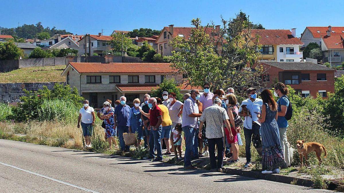 """Vecinos concentrados ayer sobre la acera que se """"esconde"""" entre la maleza en la Rúa Otero Pedrayo."""