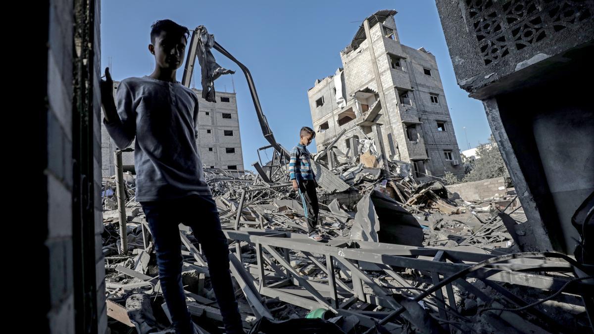 Dos neños caminen sobre les ruines d'un edificiu en Gaza.