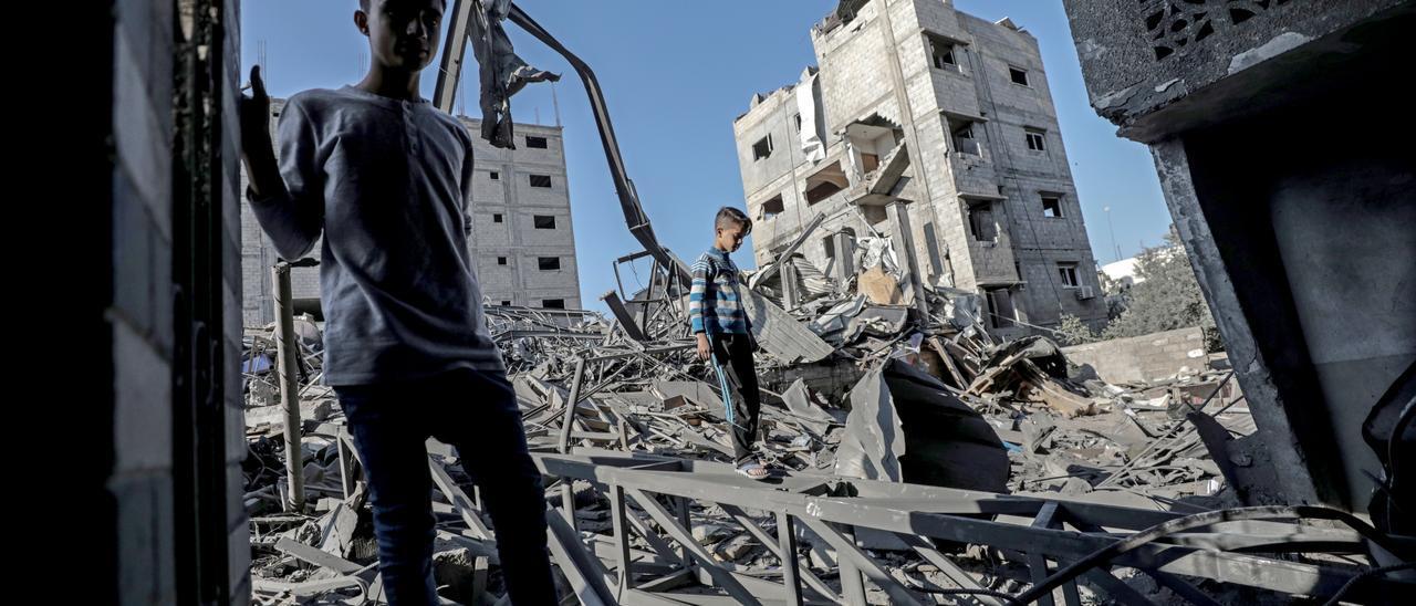 Dos niños caminan sobre las ruinas de un edificio en Gaza