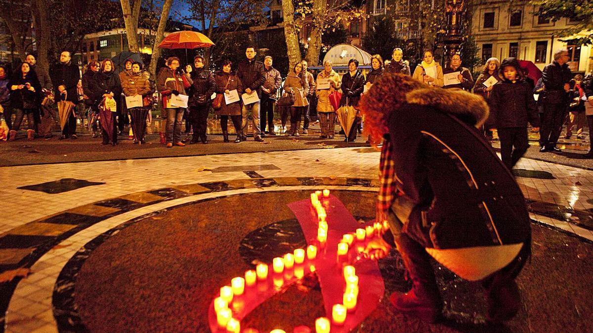 Una mujer enciende una vela en una concentración en La Felguera contra la violencia de género, en una imagen de archivo.