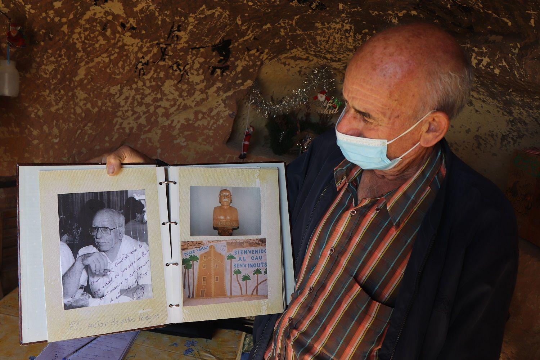 Cándido muestra un libro con imágenes de Mariano Ros