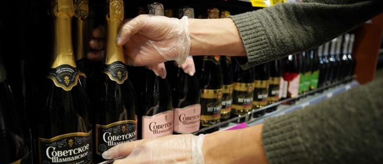 Un dependiente coloca una botella de vino espumoso ruso en un estante.
