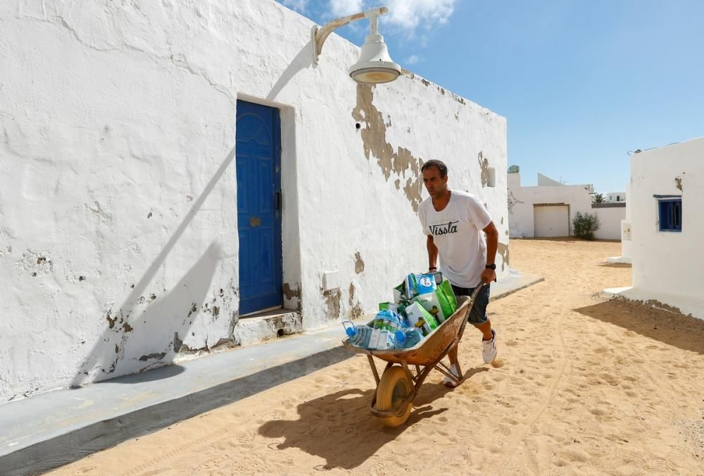 A man moves a wheelbarrow with groceries, as the ...
