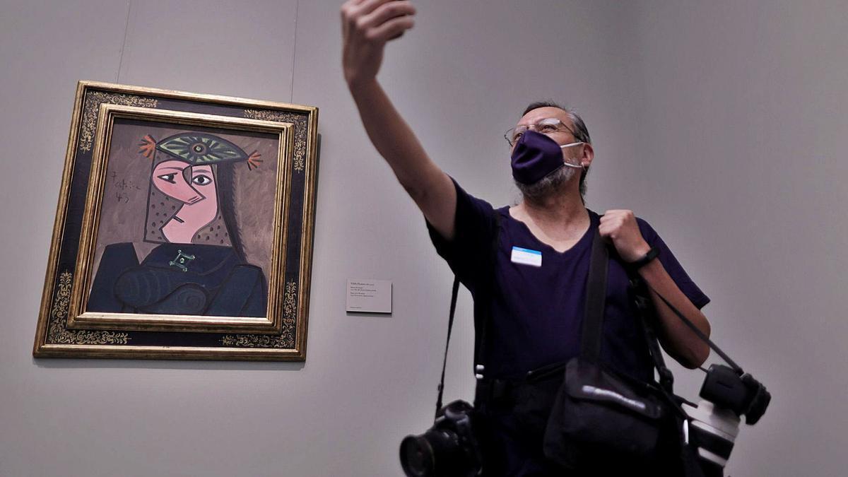 Un visitante se hace un selfi junto al cuadro de Picasso, ayer en El Prado. | |  EFE