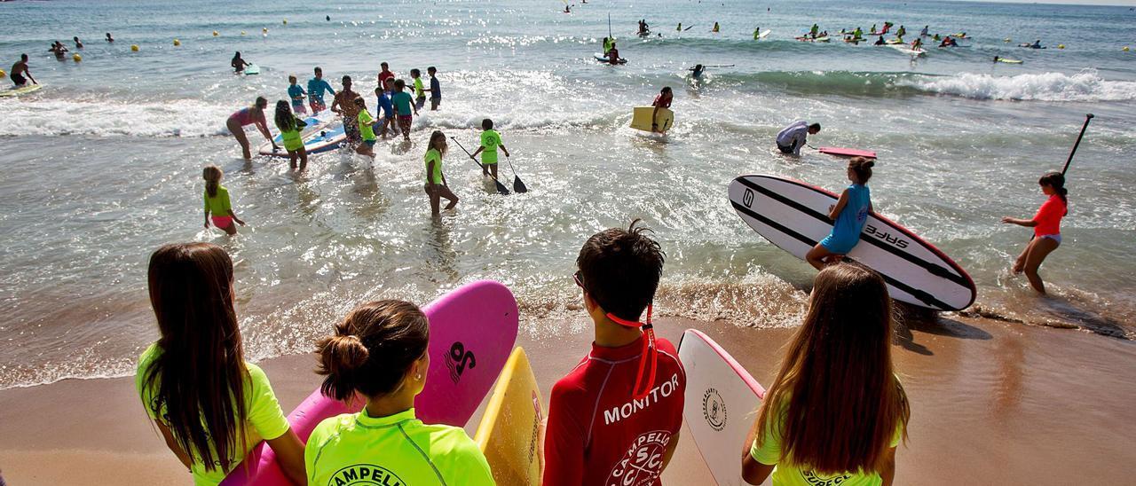Alumnos del Campello Surf Club, uno de los pioneros de la Comunidad Valenciana en deportes náuticos y que ha agotado plazas algunas semanas de este verano.   JOSE NAVARRO
