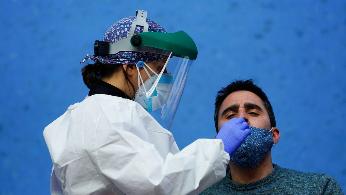 A nurse conducts a PCR test on a resident of the Basque town of Elorrio during mass testing