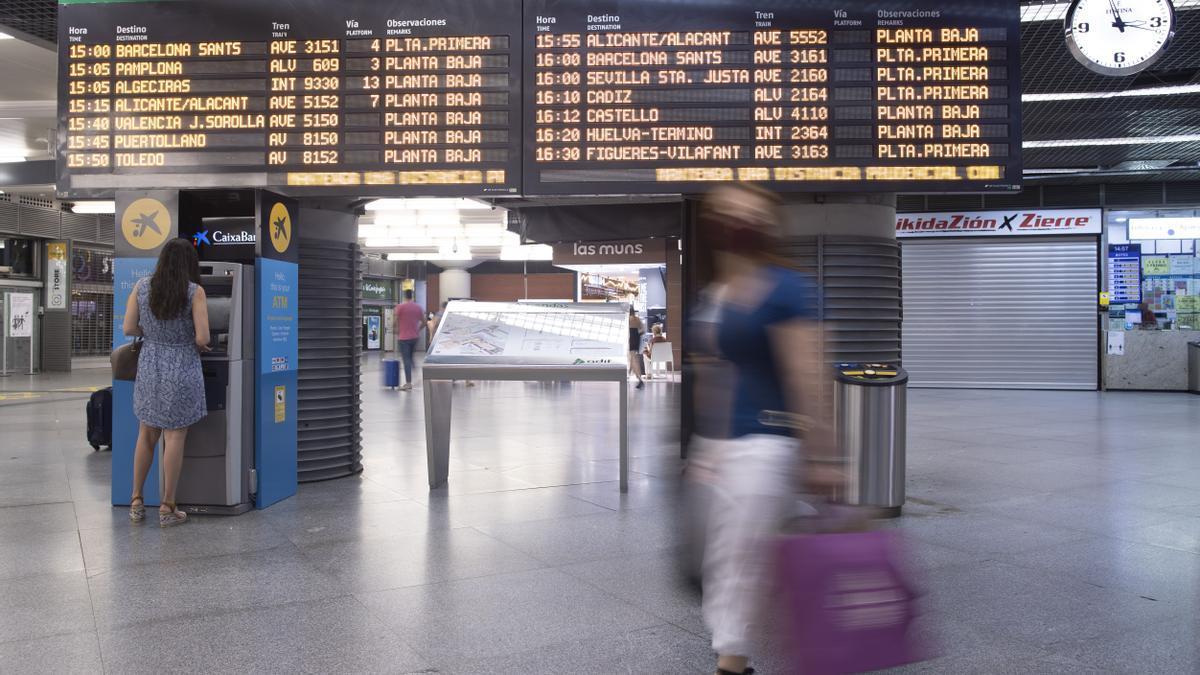 Pasajeros en el panel de salidas de la estación de AVE de Atocha.
