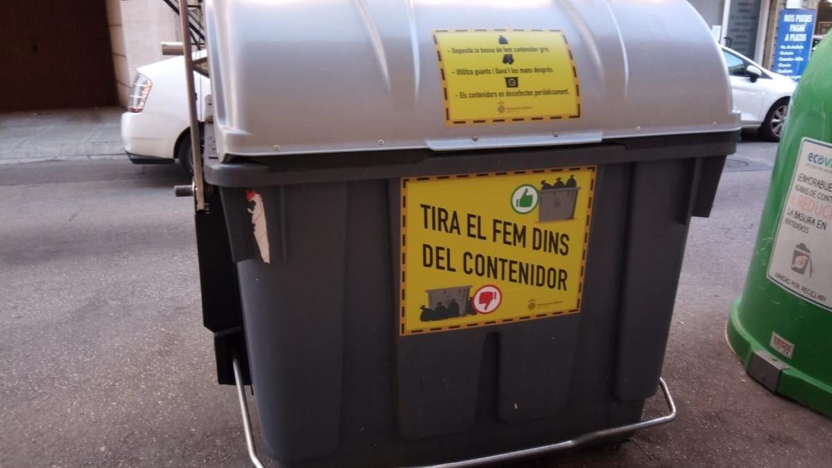 Alzira instala rótulos en los contenedores para que los vecinos dejen de tirar la basura fuera