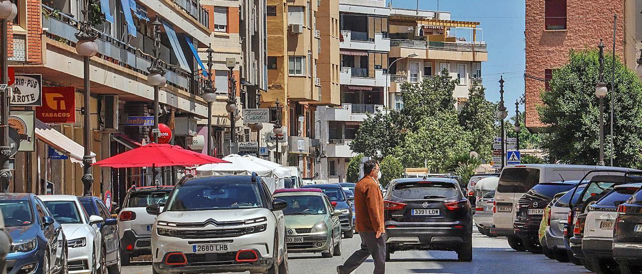 Avenida Duque de Tamames con vehículos aparcados a ambos lados y la zona de aparcamiento llena.