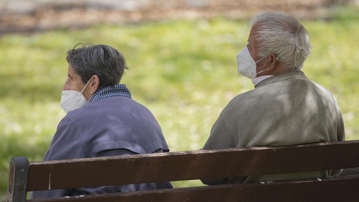 Una pareja con mascarillas sentada en un banco de un parque de Madrid