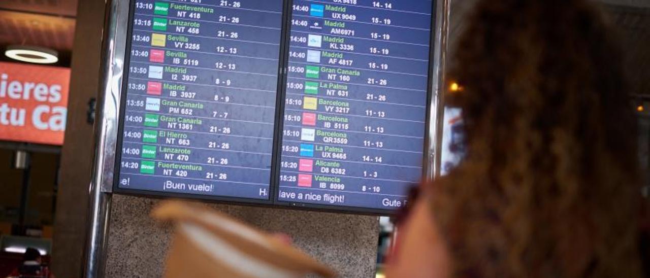 Una mujer mira el panel de información de vuelos nacionales e interislas en el aeropuerto de Tenerife Norte-Los Rodeos.     ANDRÉS GUTIÉRREZ