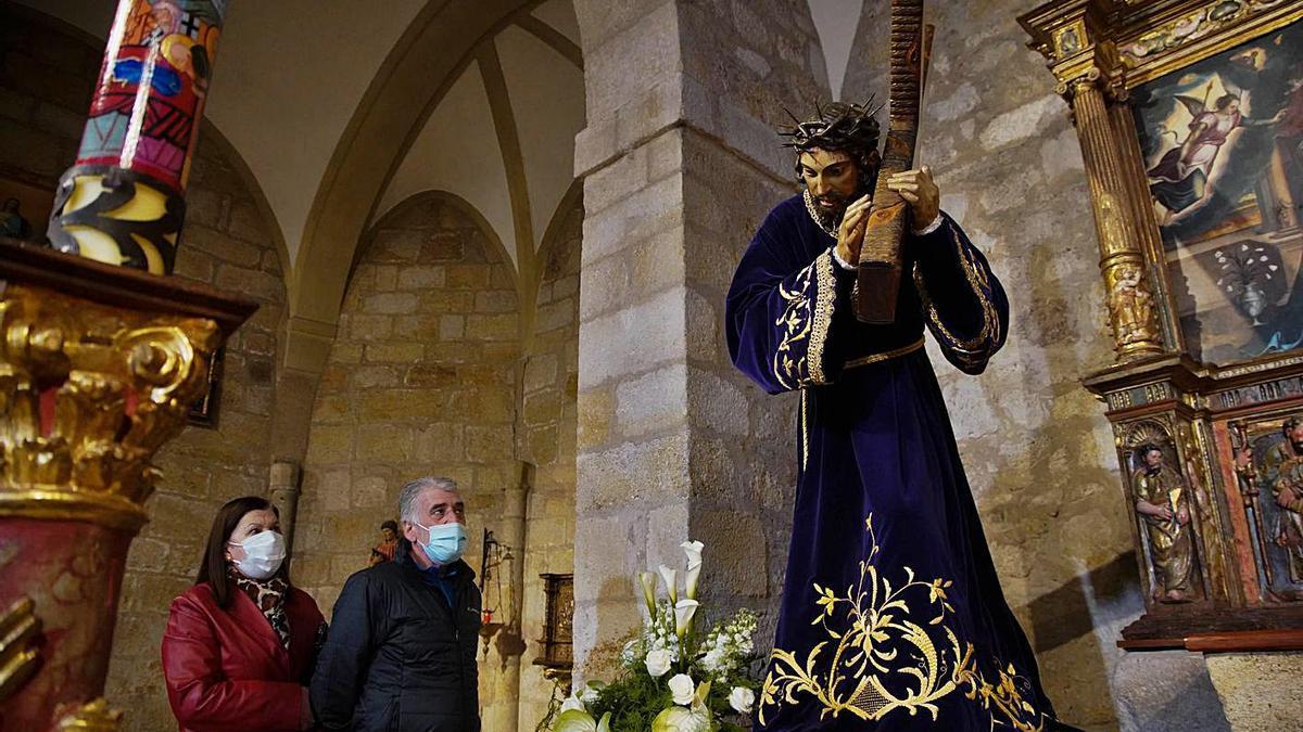 Una pareja contempla la imagen principal de la Cofradía del Vía Crucis.