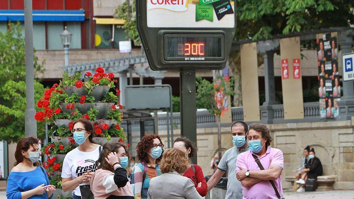 Ciudadanos con mascarilla junto a un termómetro que marca 30º en el Parque San Lázaro.