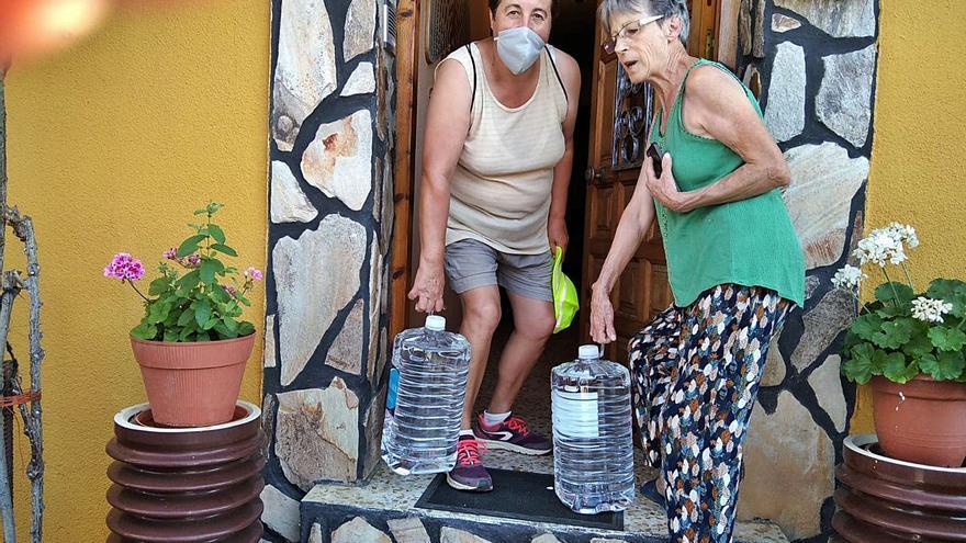Una trabajadora municipal reparte agua en un domicilio de Junquera de Tera ayer por la tarde.