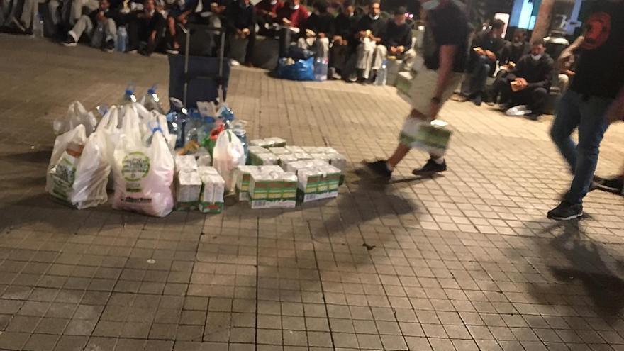 Decenas de vecinos llevan bolsas de comida a los inmigrantes acampados ante la Delegación del Gobierno en Canarias